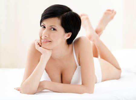 lanzamiento de bala: Mujer en ropa interior yace en la cama cómoda, fondo blanco Foto de archivo