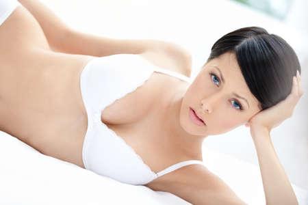 sexuality: Mujer en ropa interior miente en la cama, fondo blanco