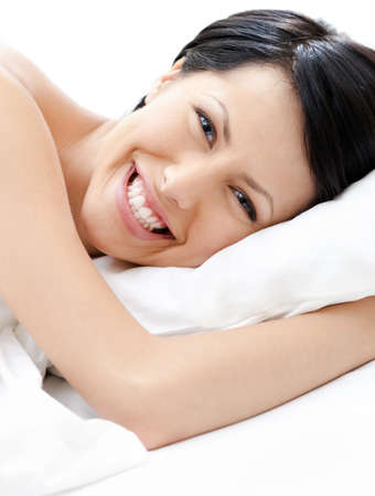 Laughing sexy woman tries to fall asleep lying at the bed photo