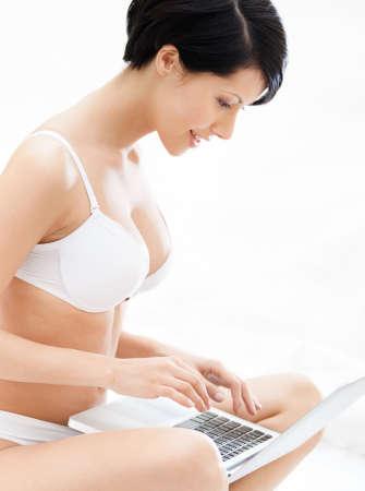 ropa interior ni�as: Mujer en ropa interior se encuentra trabajando en la computadora port�til mientras est� acostado en la cama, aislados en fondo blanco