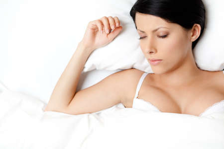 bra top: Sleeping sexy woman in the bed, white background Stock Photo
