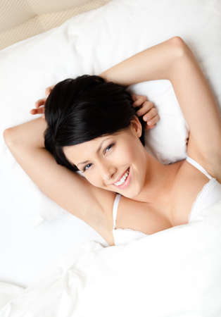 Sleeping woman in the bed with white bed linen, white background photo
