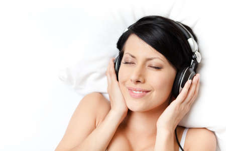 Woman in underwear listens to music through the black headphones, white background Stock Photo - 15044438