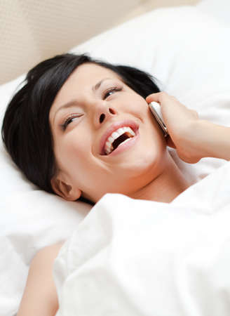 Woman in underwear speaks on phone while lying in the bed Stock Photo - 15044377