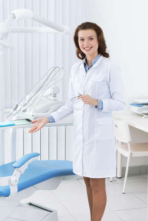 gladly: Smiley asistente m�dico muestra la silla del dentista Foto de archivo
