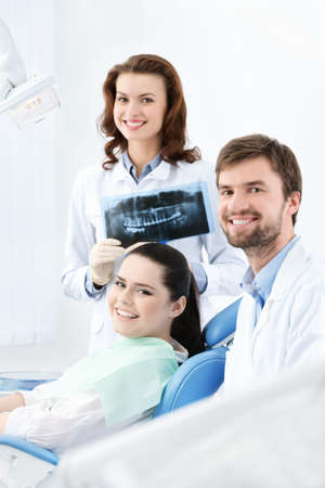 Dentist, assistant and client are satisfied of their work photo