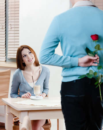 Man keeps red rose behind his back to present it to his girlfriend photo