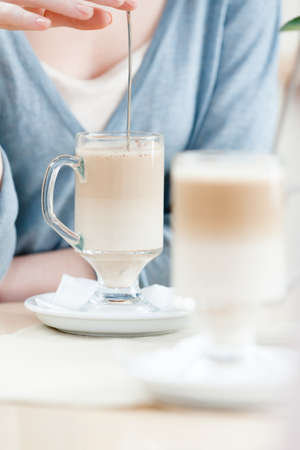 Woman is stirring the milk cocktail at the cafe Stock Photo - 15498489