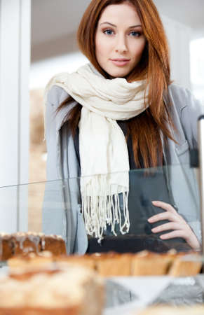 Woman in scarf looking at the bakery window full of different pieces of cakes photo