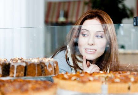 look inside: Woman in scarf looking at the bakery showcase full of different pieces of pies Stock Photo