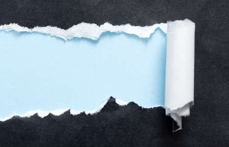 curled paper: Torn black paper edge with blue space for your message