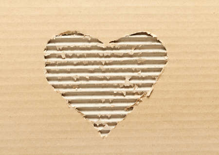 crimped: Ripped heart shaped corrugated cardboard, brown background