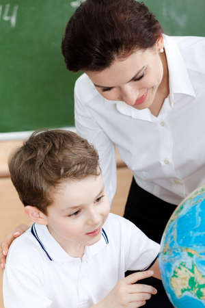 Little schoolboy studies geography with teacher photo