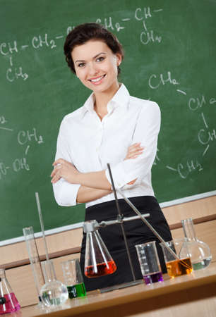 short: Smiley chemistry teacher with crossed arms at the classroom