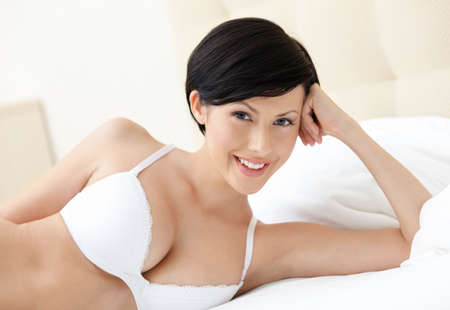 head down: Smiling woman in underwear is lying in the wide bed Stock Photo