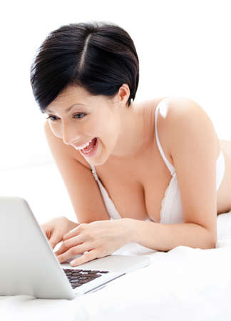 Woman in underwear is working on the silver laptop while lying on the bed, isolated on white background photo