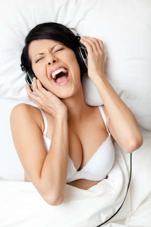 Woman in bra listens to music through the earphones, white background photo