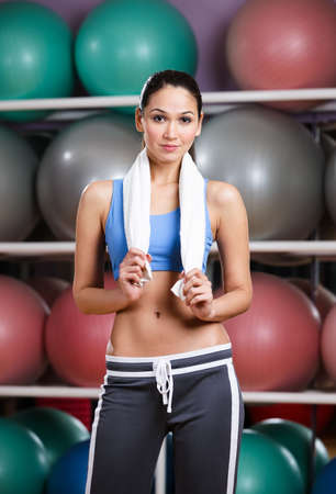 Athletic woman with perfect figure in fitness gym with shelves of gym balls photo