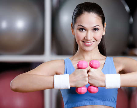 Athletic woman in sportswear training with dumbbells in gym to have ideal muscles Stock Photo - 15177345