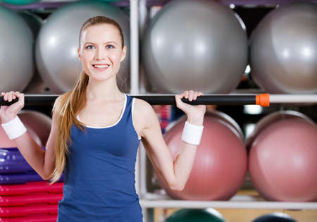 Athletic woman in sportswear works out with gymnastic stick Stock Photo - 15177348