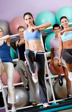 girl in sportswear: Sexy female coach exercises with her group on step boards at the gym in a sports class Stock Photo