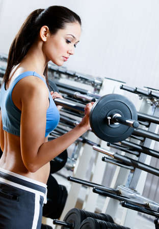 Woman with dumbbells in sport centre photo
