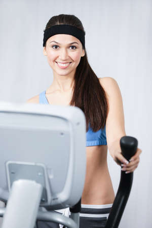 simulators: Young sportswoman training on simulators in gym