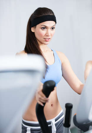 Young athletic woman training on training apparatus in gym Stock Photo - 15177343