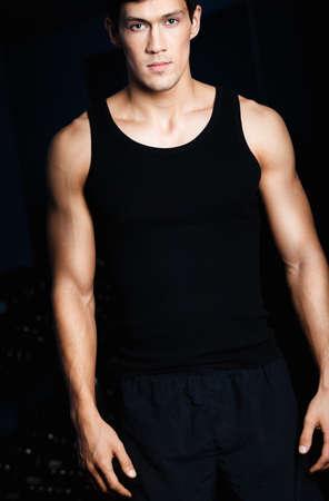 sports wear: Portrait of a serious sportive man in sportswear isolated on black background