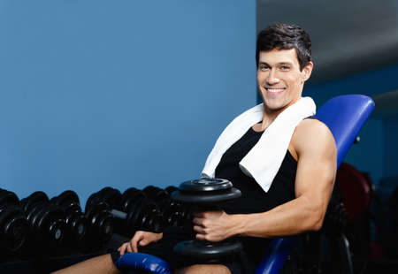 athletic wear: Athletic man in sports wear rests holding a weight in the hand against a set of dumbbells Stock Photo
