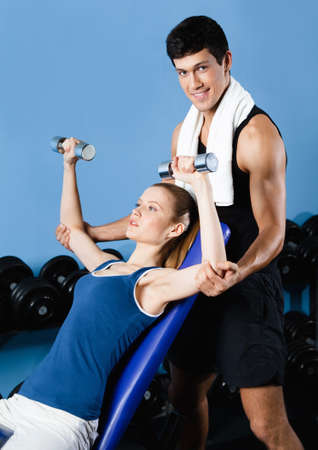 Trainer helps woman to exercise with dumbbells in gym photo