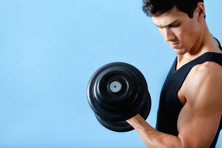 heave: Handsome muscular man uses his dumbbell to exercise flexing bicep muscle