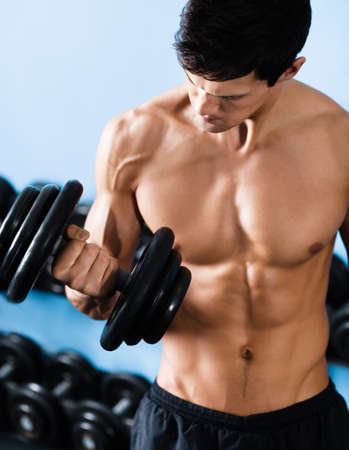 Handsome muscular man with nude body uses his dumbbell to exercise flexing bicep muscle photo