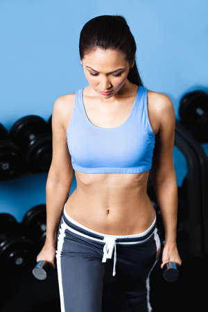 ideal: Athletic woman works out with dumbbells in fitness gym Stock Photo