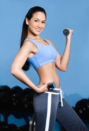 ropa deportiva: Mujer deportista trabaja con pesas en un gimnasio de entrenamiento Foto de archivo