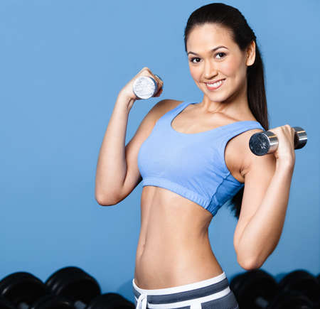 ropa deportiva: Deportista se resuelve con pesas en la clase de gimnasia