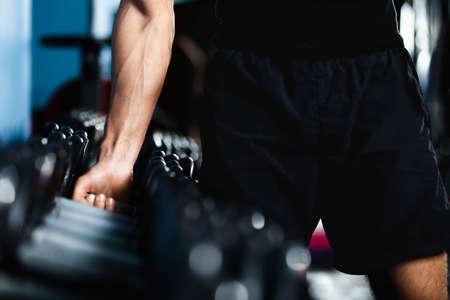 actividad fisica: Mano de un hombre que elige una mancuerna de conjunto de pesas negras Foto de archivo