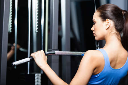 back exercise: Athletic young woman works out on training apparatus in fitness gym Stock Photo