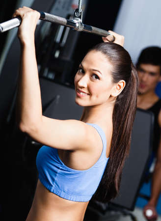 Athletic young woman works out on simulator in fitness gym photo