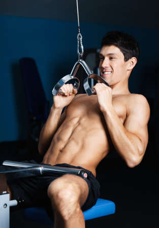 Athletic young man works out on simulator in gym class Stock Photo - 15177373