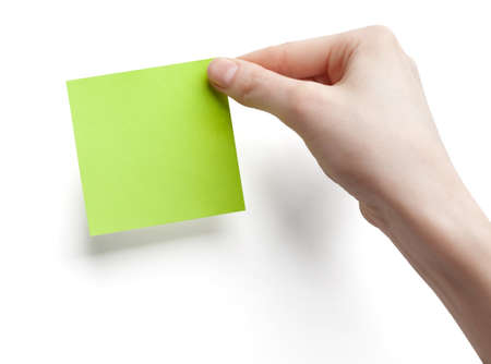 reminder concept: Green post-it note with hand on white background