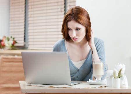cafe internet: La mujer se est� trabajando en el pc en el caf� internet