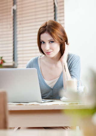 Woman is working on the pc at the internet shop photo