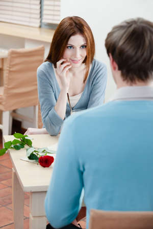 Man and woman are at the coffee house table with rose near them photo