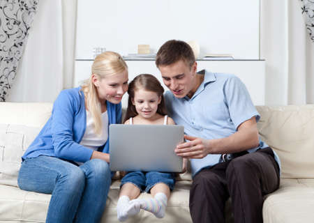 Happy family sit on the couch with laptop having a rest photo