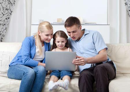 gladly: La familia feliz se sienta en el sof� con el ordenador port�til que tiene un resto