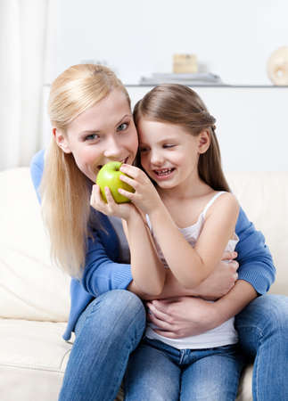 Smiley mother with her eating green apple daughter photo