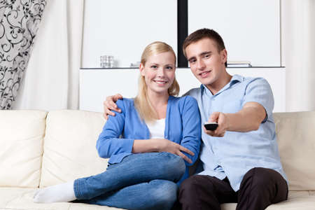 Sitting on the white couch couple is going to watch TV set together photo