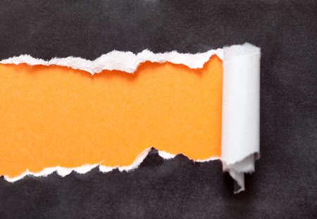 tårar: Sönderrivet papper med orange utrymme för ditt meddelande. Svart bakgrund Stockfoto