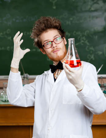 medical scientist: Mad professor in glasses admires his experimental red liquid